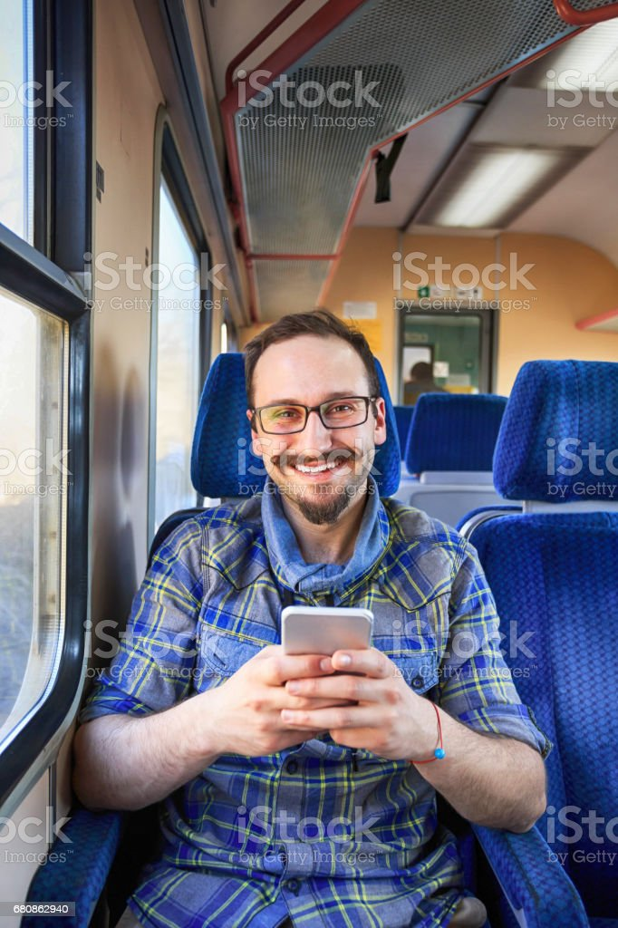 Smiling young man using smart phone inside of a trian. Looking at...