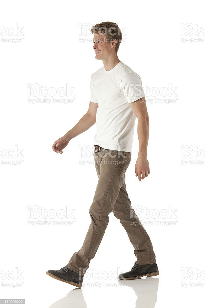 Smiling young man walking stock photo