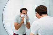 istock Smiling young man washing face in morning in bathroom 1248276552