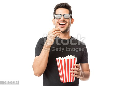 istock Smiling Young Man Watching 3D Movie While Eating Popcorn 1048532298