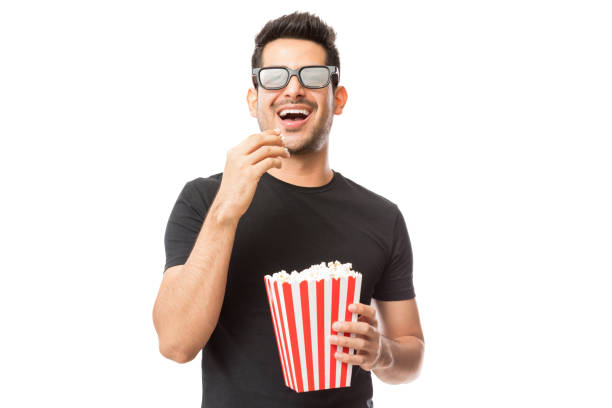 Smiling Young Man Watching 3D Movie While Eating Popcorn Smiling young man watching 3D movie while eating popcorn on white background 3 d glasses stock pictures, royalty-free photos & images