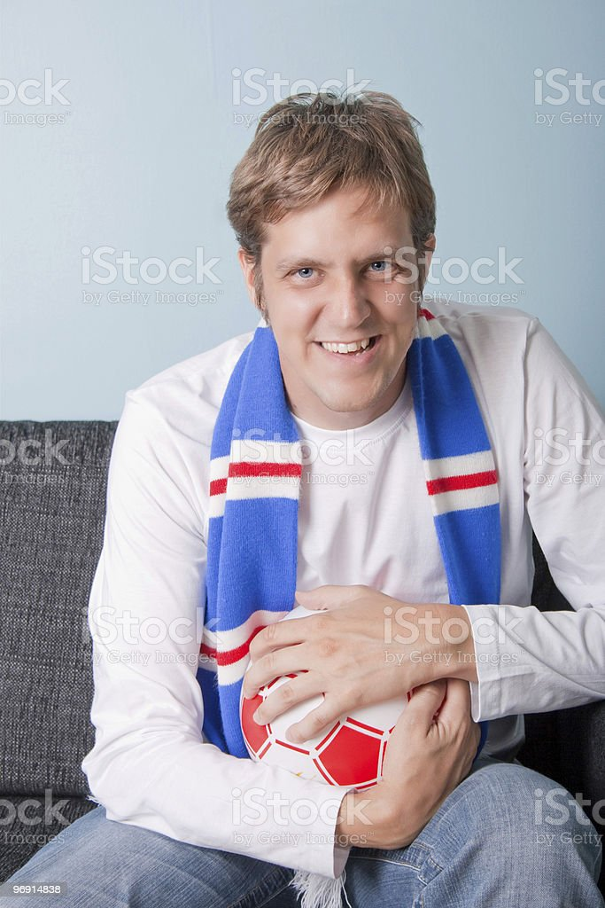 Smiling young man watching football royalty-free stock photo