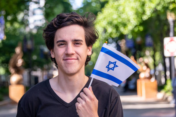 Smiling young man waving the Israeli flag Smiling young man waving the Israeli flag looking at the camera judaism stock pictures, royalty-free photos & images