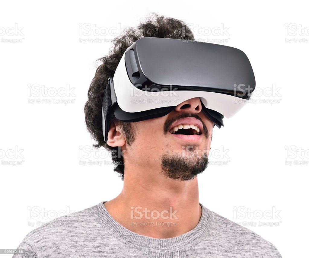Smiling young man wearing vr headset - Photo