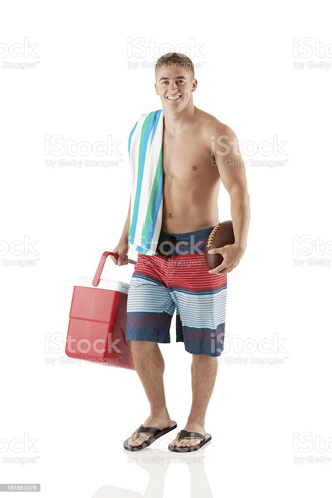 Smiling young man with a cooler and football royalty-free stock photo