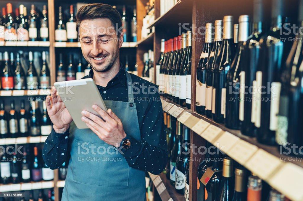 Sourire de jeune homme avec une tablette numérique dans un magasin de vin - Photo de Adulte libre de droits