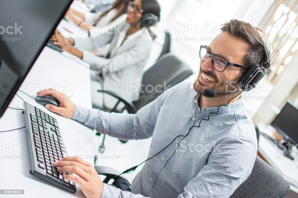 Smiling young man with headset using computer in call center.