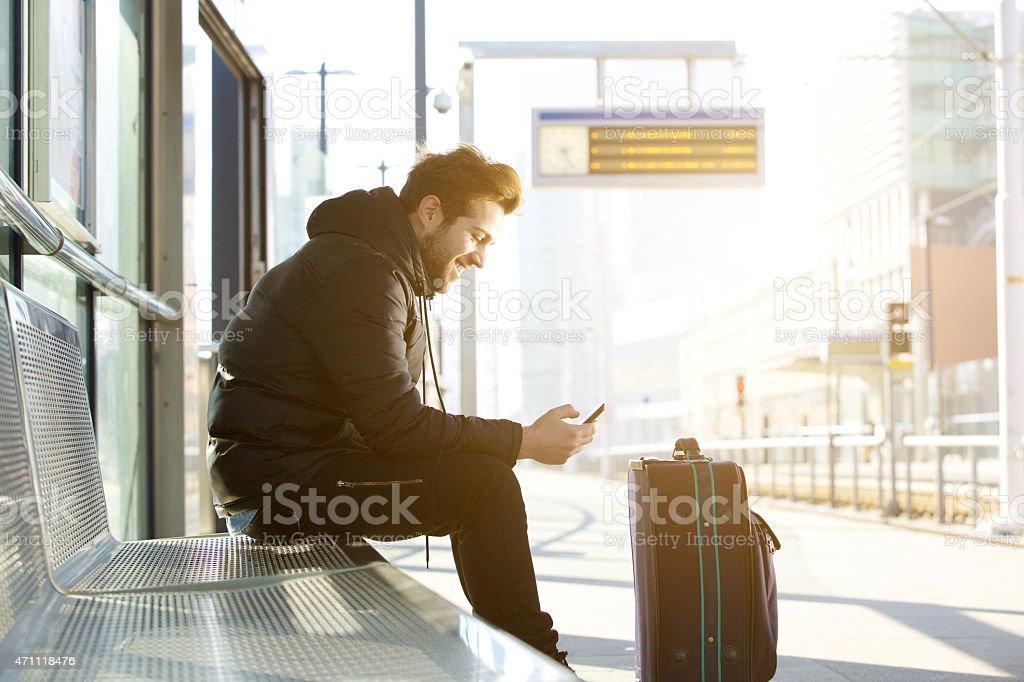 Lächelnder, junger Mann mit Handy und Tasche – Foto