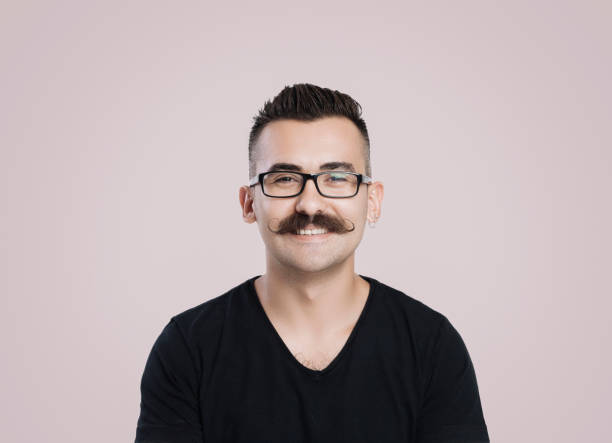 Smiling young man with mustache Young male with glasses and mustache, grey background, studio shot, smiling mustache stock pictures, royalty-free photos & images