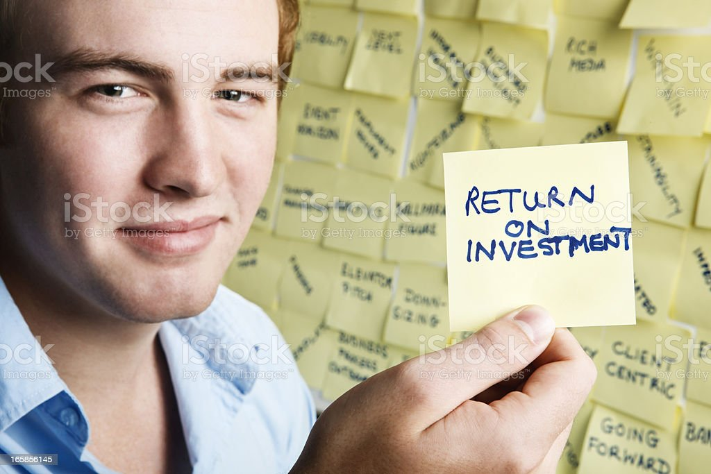 Smiling young man with return on investment note royalty-free stock photo