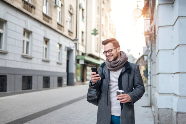 Smiling young man with takeaway coffee and smart phone walking in the town street on winter day. stock photo