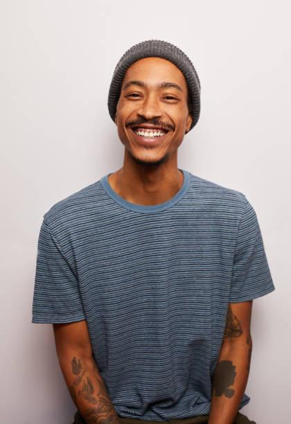 Lächelnder junger Mann mit Tätowierungen vor grauem Hintergrund – Foto