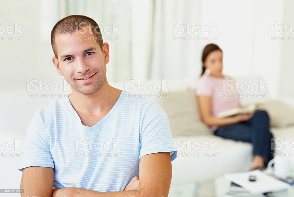 Smiling young man with wife in the background at home royalty-free stock photo