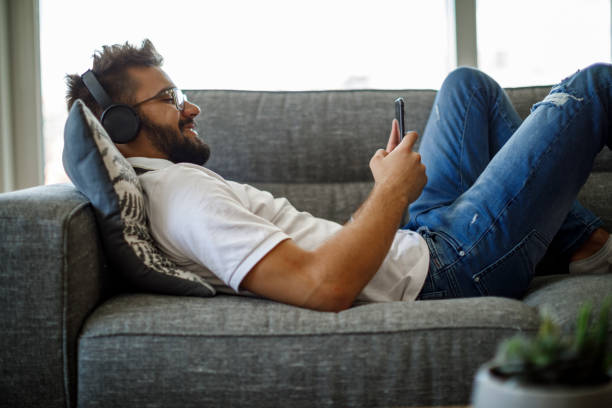 Smiling young man with wireless headphones using smart phone on sofa stock photo