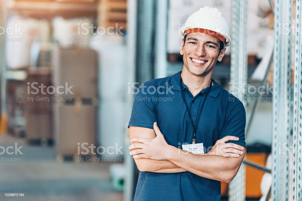 Smiling young man with work helmet in a warehouse stock photo