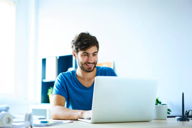 Smiling young man working on laptop in home office stock photo