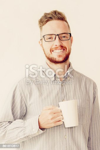 istock Smiling young manager in glasses drinking coffee 861810812