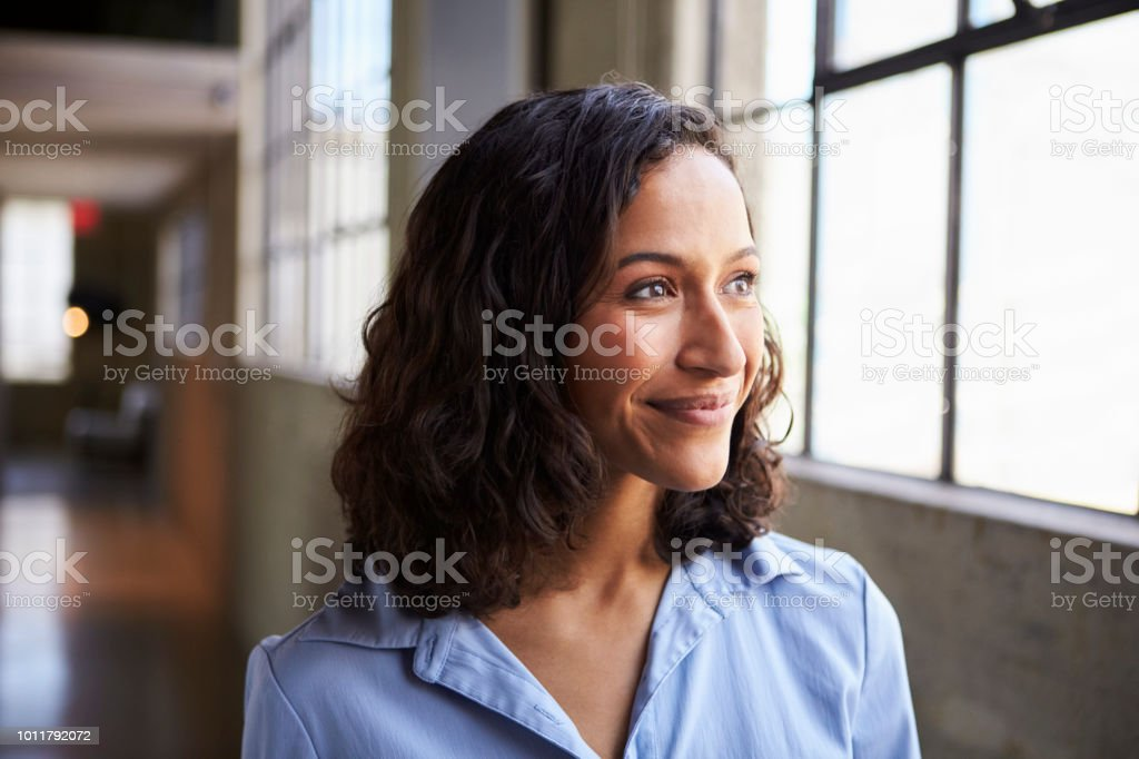 Smiling young mixed race businesswoman looking away stock photo