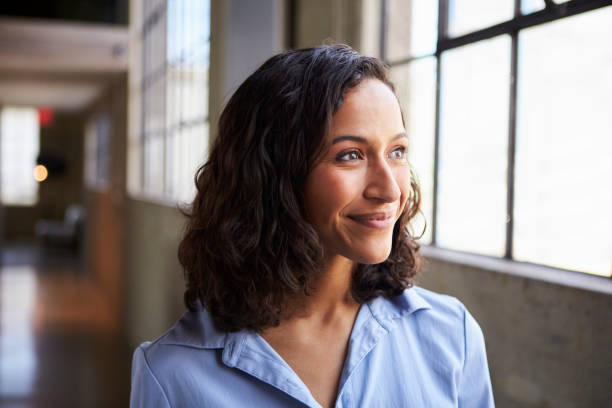 Smiling young mixed race businesswoman looking away Smiling young mixed race businesswoman looking away looking away stock pictures, royalty-free photos & images