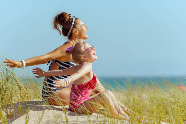 smiling young mother and child on seacoast rejoicing stock photo