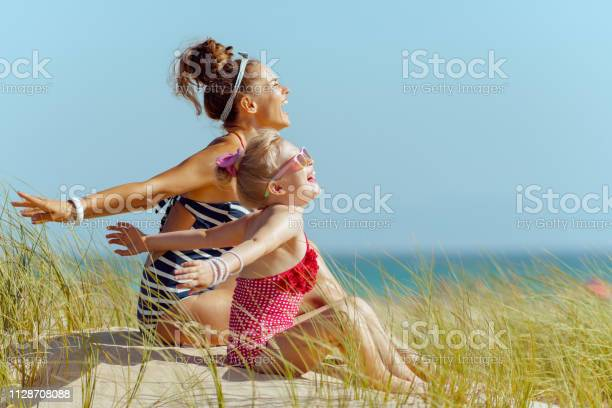 Photo of smiling young mother and child on seacoast rejoicing
