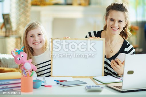 smiling young mother and child in striped sweaters in home office in the modern living room in sunny day showing blank billboard.