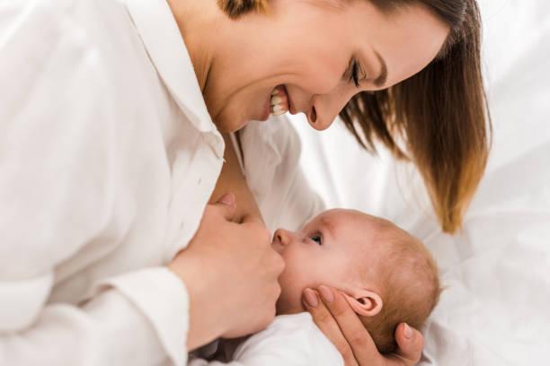 smiling young mother in white t-shirt breastfeeding baby - amamentação imagens e fotografias de stock