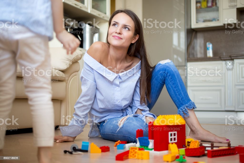Smiling young mother or nanny looking at her child stock photo