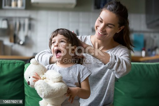 1063760138 istock photo Smiling young mum making ponytail to little daughter 1063760118