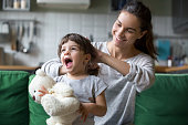 istock Smiling young mum making ponytail to little daughter 1063760118
