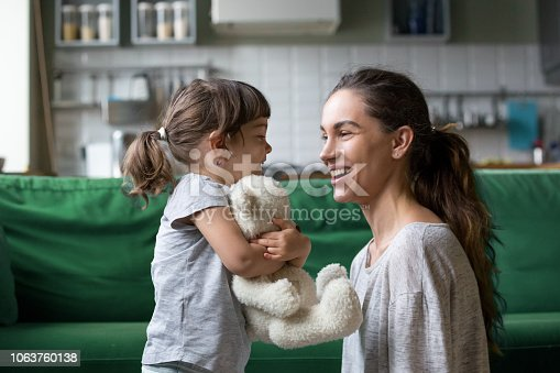 Smiling young loving mum talking with little preschool daughter with favorite stuffed toy, playing in living room at home, mother laughing with child, babysitter playing with pupil