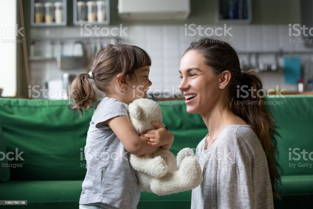 Smiling young mum talking with little daughter stock photo
