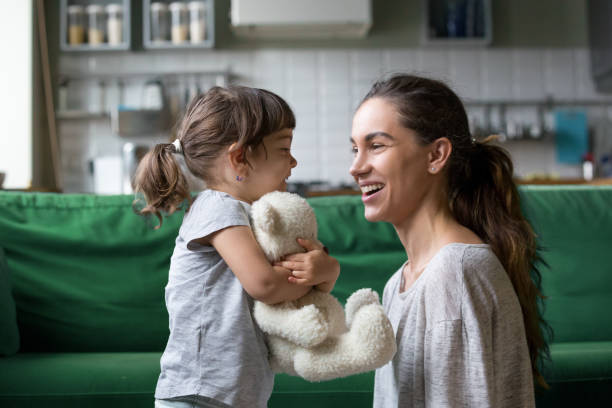 smiling young mum talking with little daughter - mother stock pictures, royalty-free photos & images