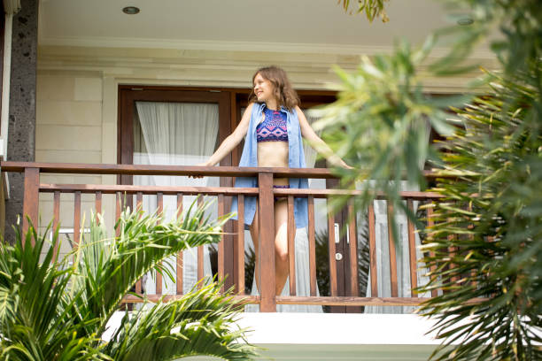 Smiling Young Nice Woman in Swimsuit on Balcony stock photo
