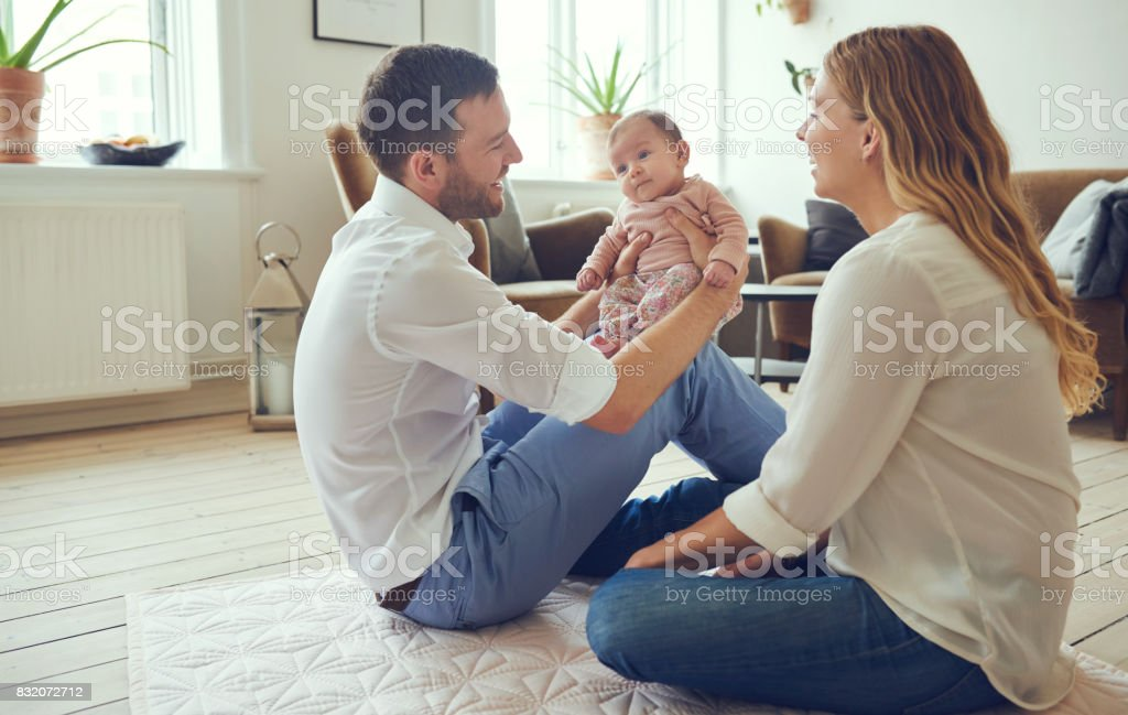 Smiling young parents sitting with their baby girl at home stock photo