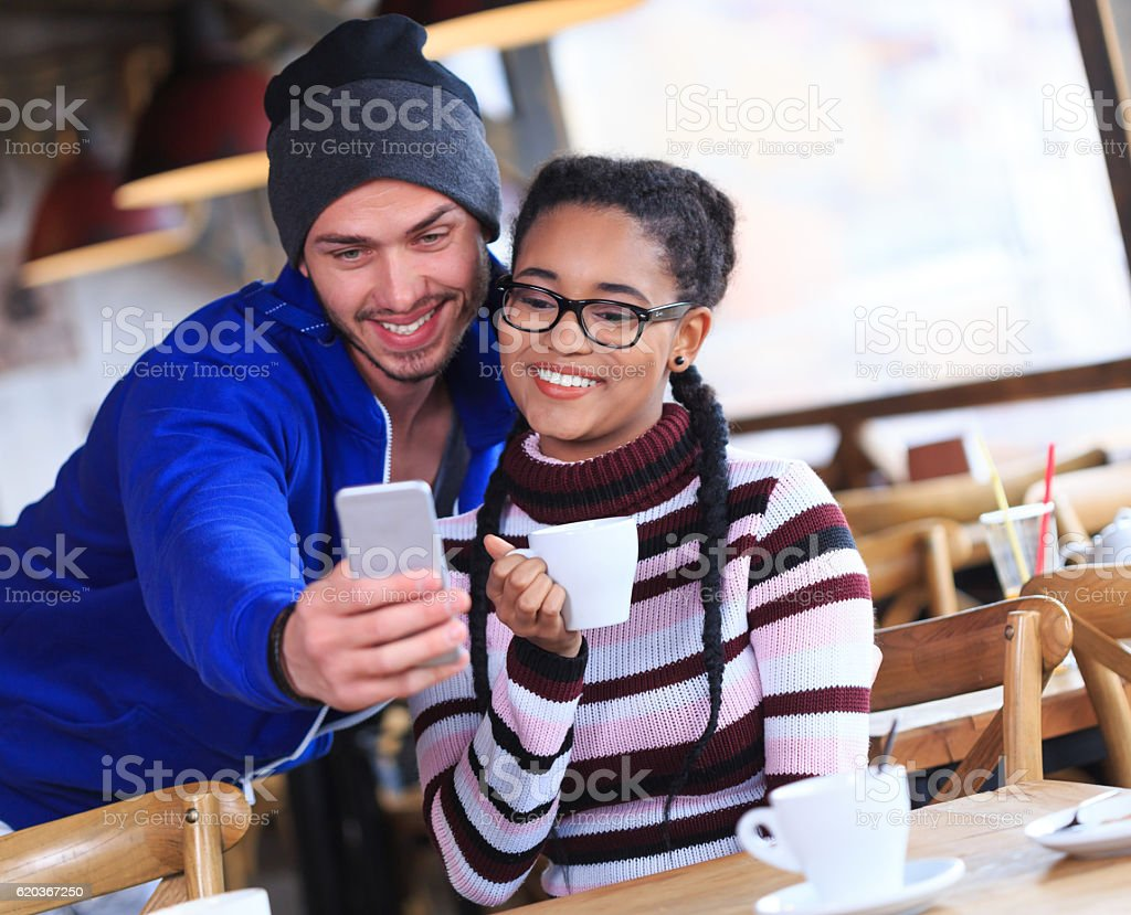Smiling young people making selfie in a bar zbiór zdjęć royalty-free