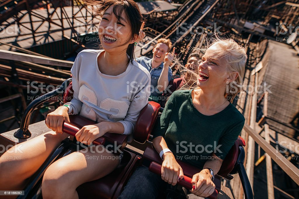 Smiling young people riding a roller coaster - foto de stock