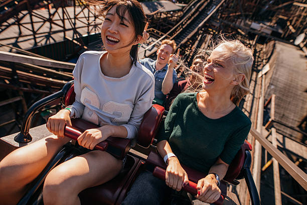 smiling young people riding a roller coaster - roller coaster stock pictures, royalty-free photos & images