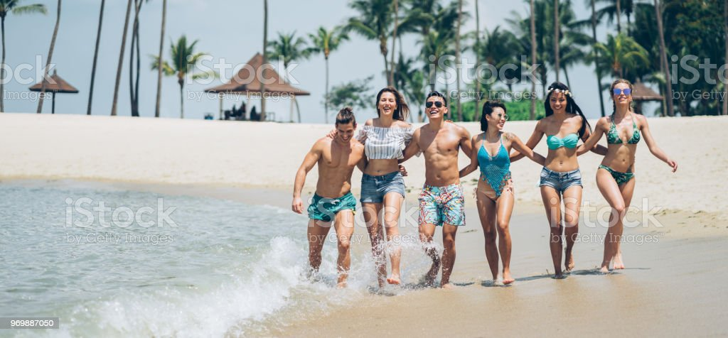 Smiling young people running on the beach stock photo
