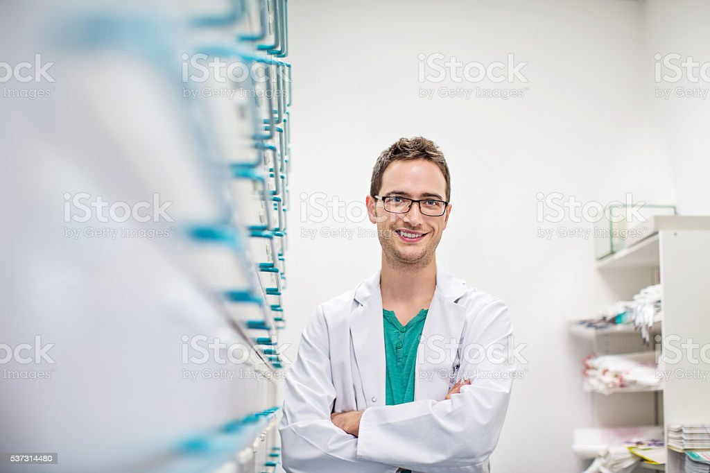 Smiling young pharmacist leaning to a medicine rack stock photo