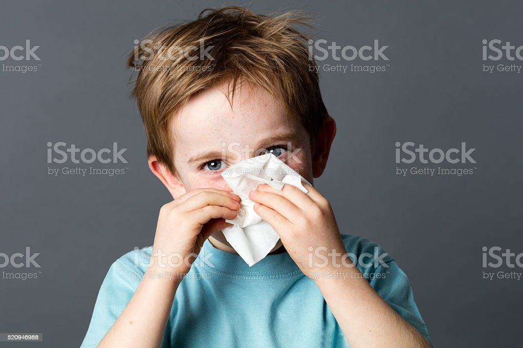 smiling young preschooler with a tissue for cold or rhinitis stock photo