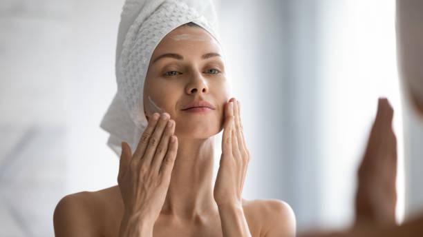 Sonriente joven cita bonita envuelta en toalla alisando la piel perfeccionando. - foto de stock