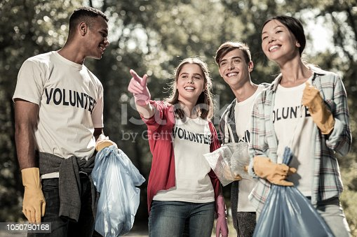istock Smiling young pupils feeling involved in cleaning up the forest and volunteering 1050790168
