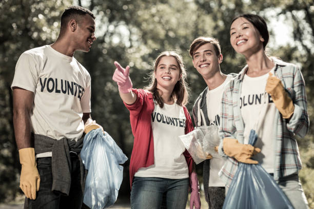 Smiling young pupils feeling involved in cleaning up the forest and volunteering stock photo