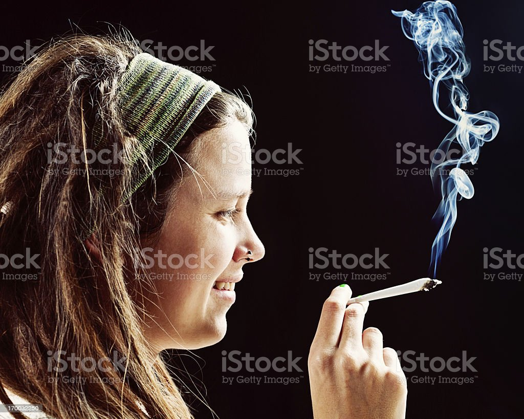 Smiling young rasta girl holds hand-rolled reefer stock photo