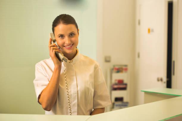 Joven recepcionista sonriente hablando por teléfono en el mostrador de pago - foto de stock