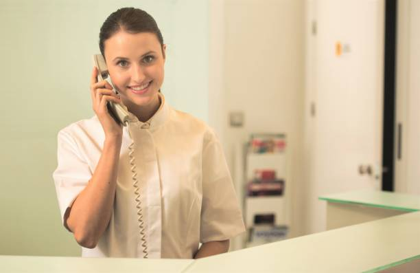 Smiling young receptionist talking on phone at checkout counter stock photo