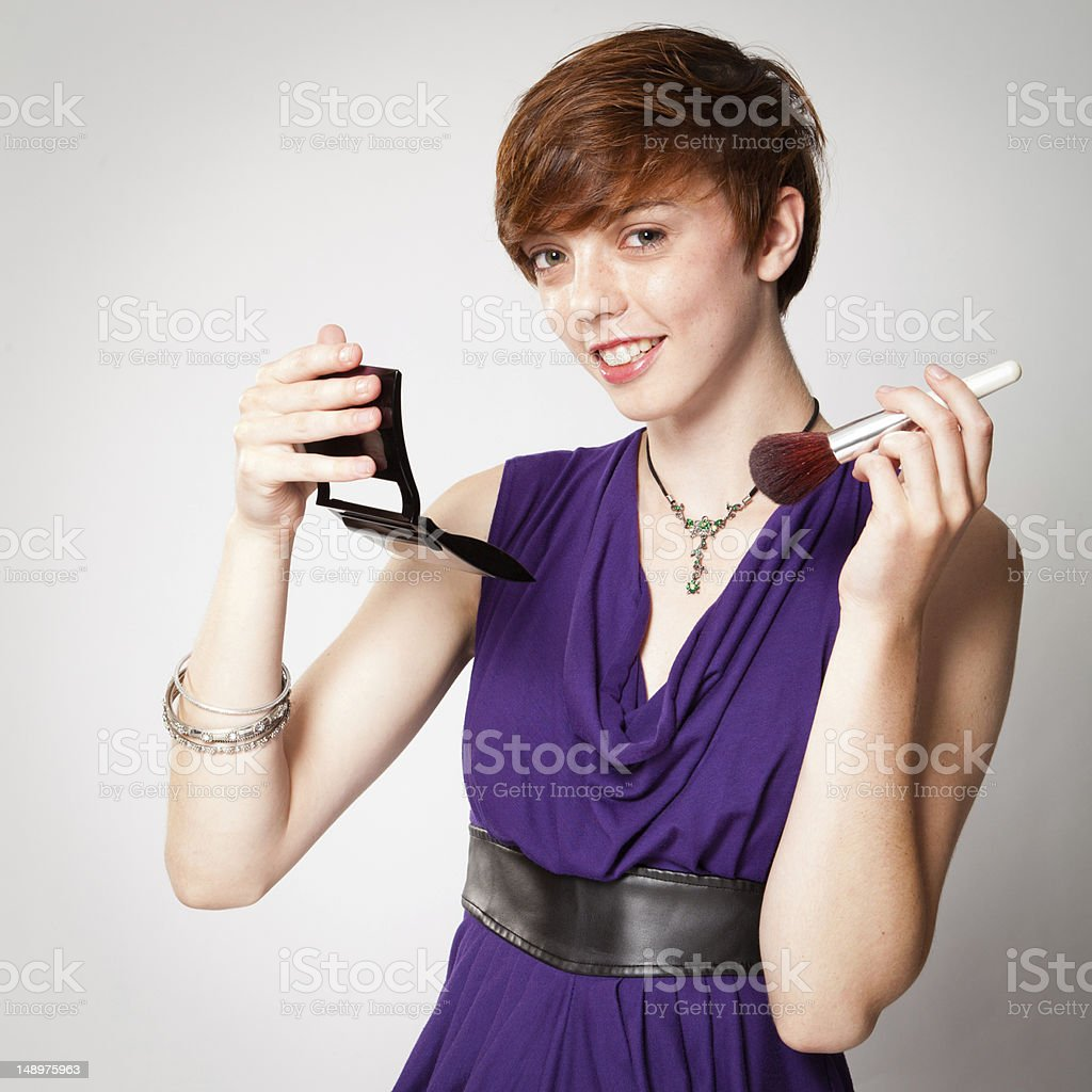 Smiling Young Red-Haired Woman Applying Makeup stock photo