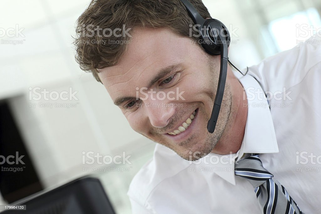 Smiling young salesman working with headset on stock photo