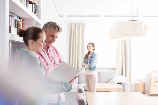 Lächelnde junge Verkäuferin und männliche Kundin mit Blick auf Blaulicht, während Frau in der Wohnung steht – Foto